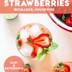 Strawberry gin mojito poured in a low ball glass topped with ice cubes, strawberries and fresh mint.