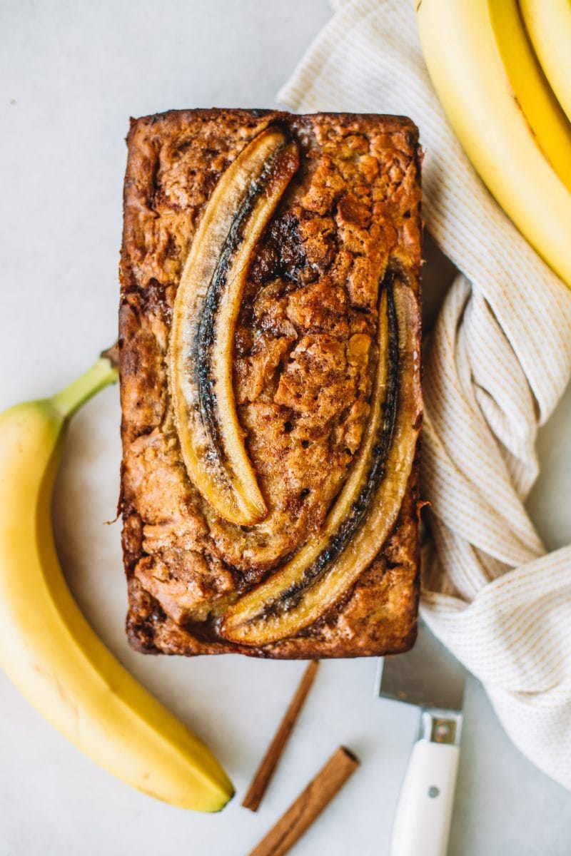 Banana bread baked with two sliced bananas on top.