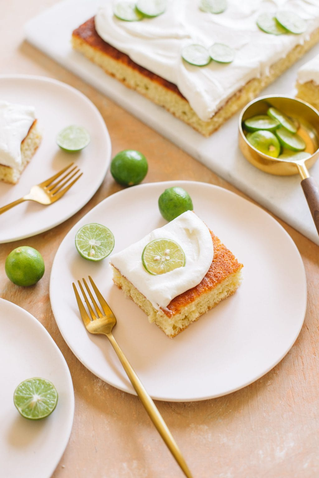 A piece of key lime cake served on a small pink plate with a gold fork.