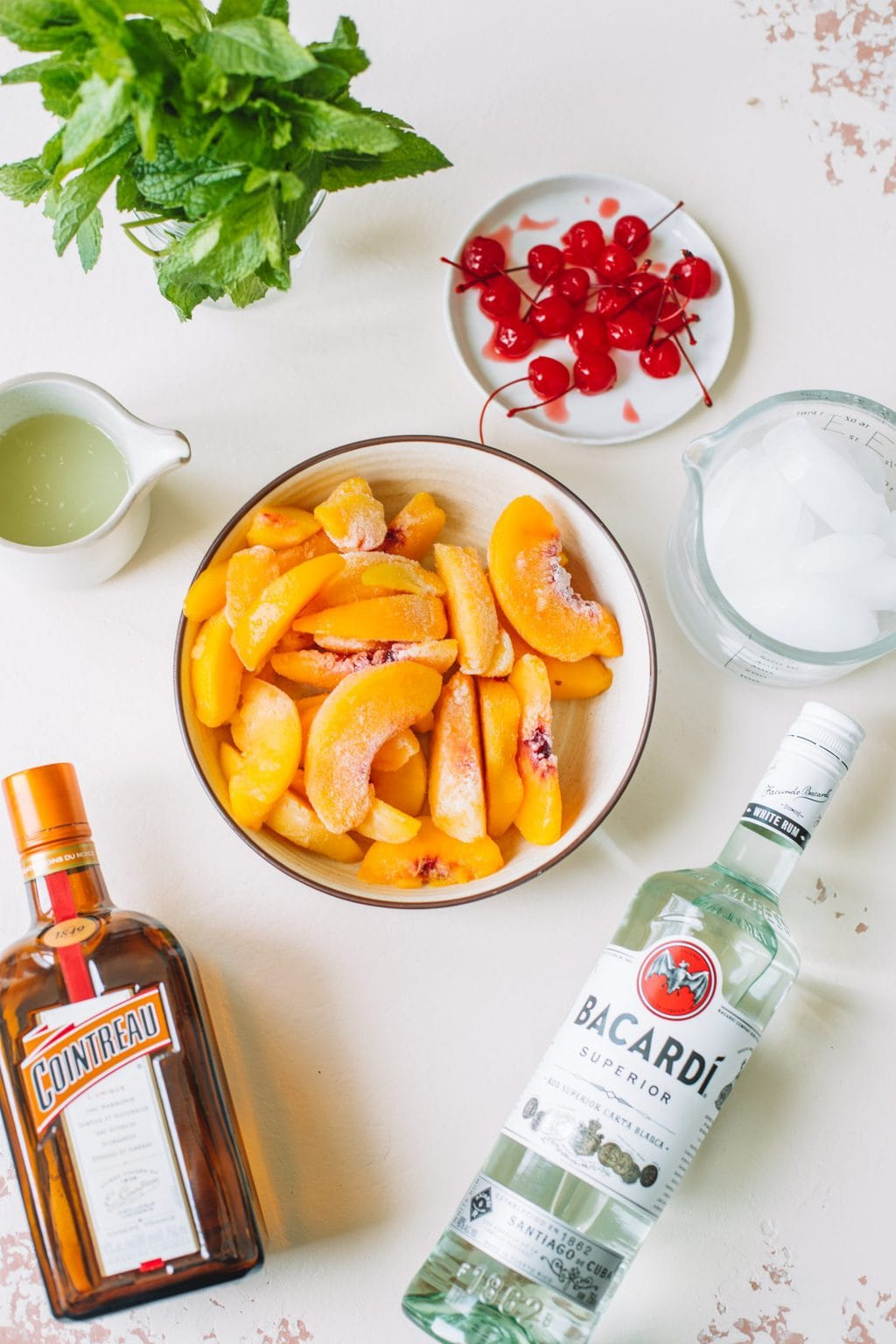 frozen peaches in white bowl, bacardi white rum, cointreau, lime juice, ice cubes, maraschino cherries