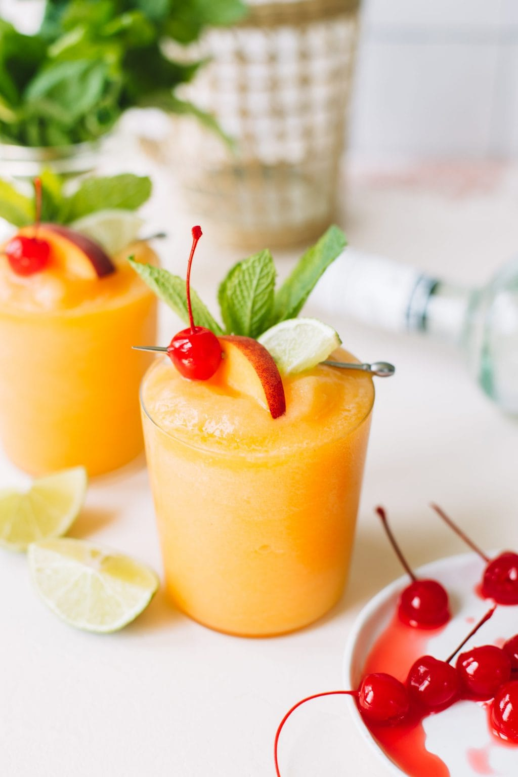 two frozen peach daiquiris with cherry and lime garnish in glasses