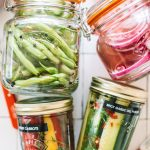 pickled green beans, red onions, carrots and cucumbers in glass jars