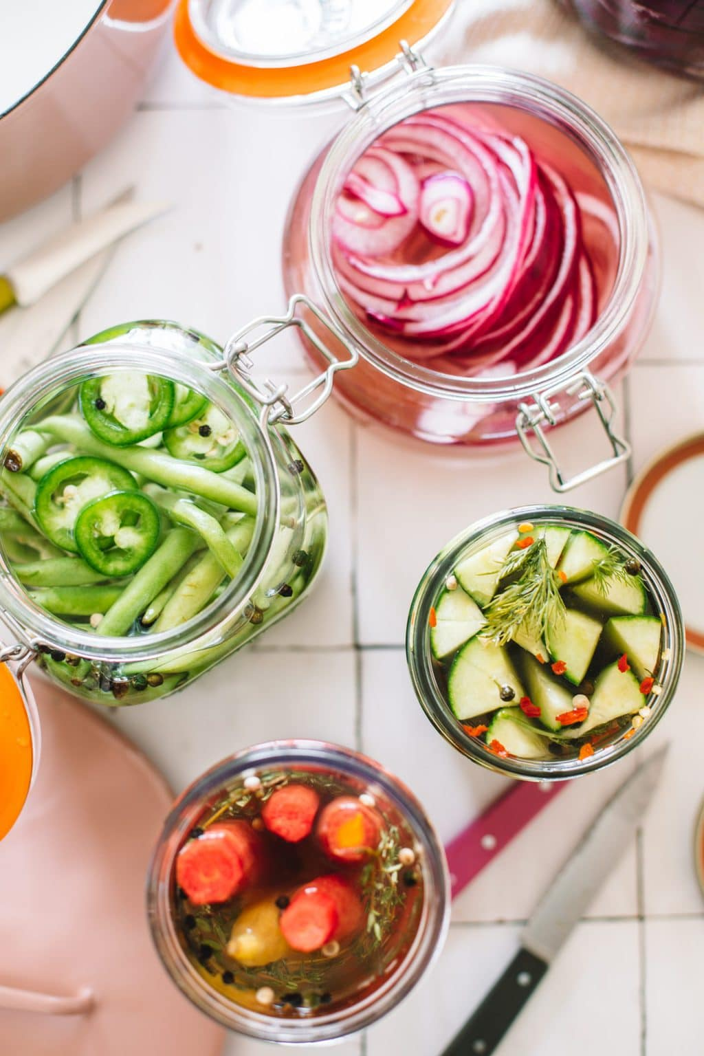 pickled green beans, red onions, carrots and cucumbers in open glass jars