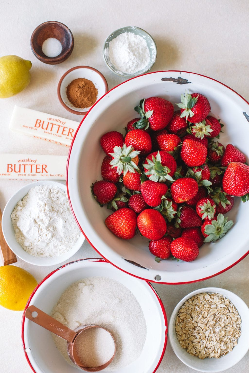 fresh strawberries in white bowl, butter sticks, cinnamon, sugar, flour, cornstarch, oats, lemon