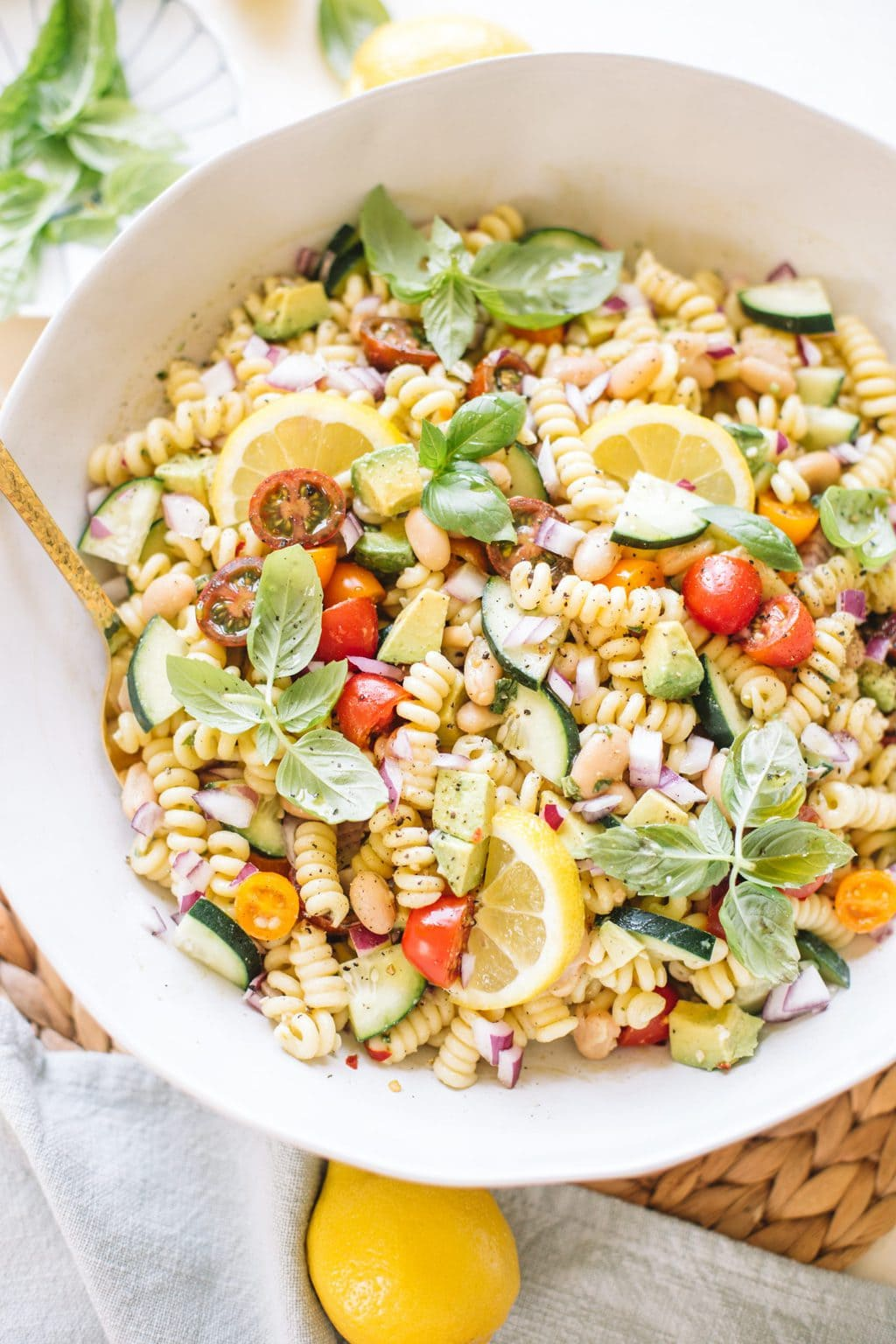 easy pasta salad with beans, avocado, cucumbers, tomatoes, basil in white bowl