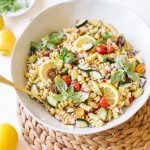 vegan pasta salad with cucumbers, tomatoes, basil in white bowl