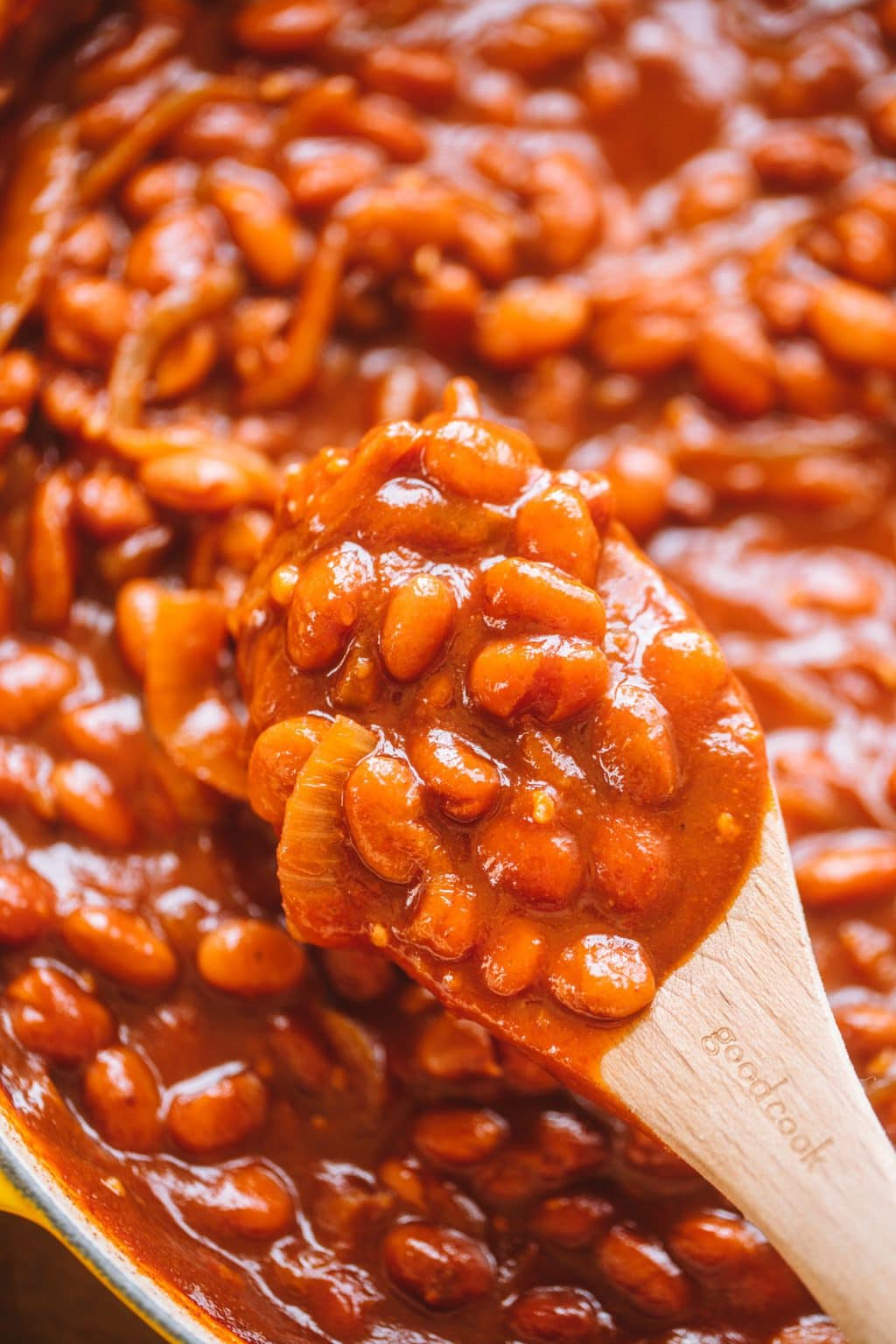 homemade baked beans in pot with wooden spoon