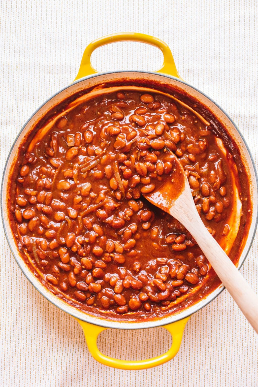 vegetarian baked beans in yellow dutch oven with wooden spoon