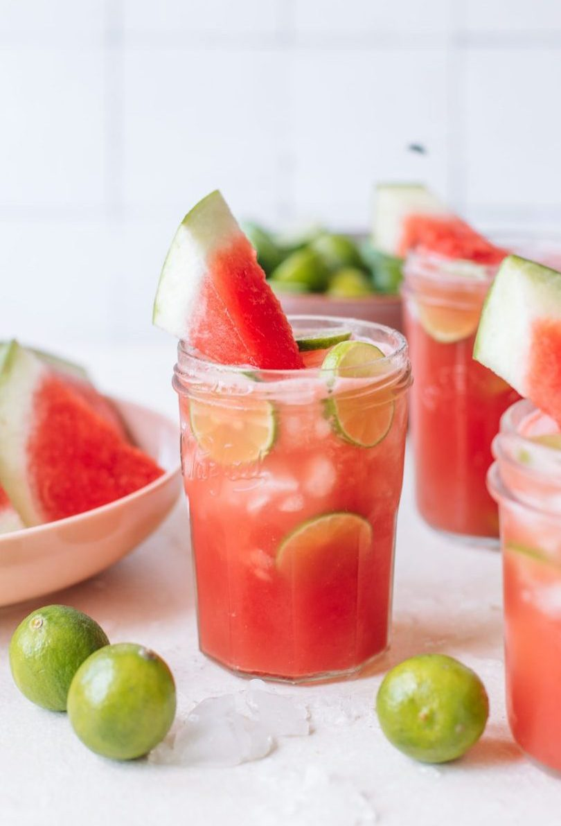 A mason jar filled with watermelon vodka drink topped with watermelon chunks and lime wheels.