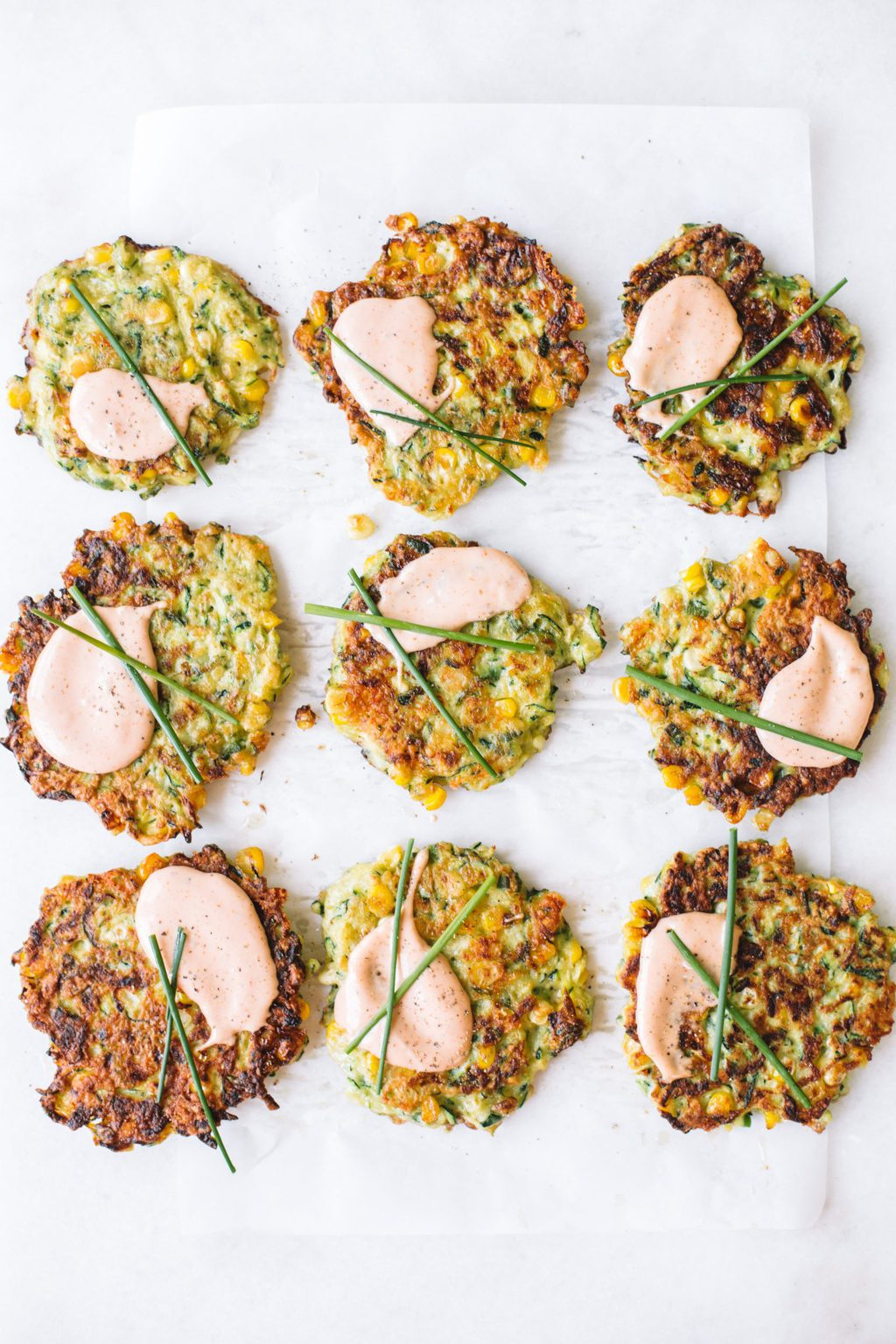 zucchini corn fritters on parchment paper topped with dipping sauce and chives