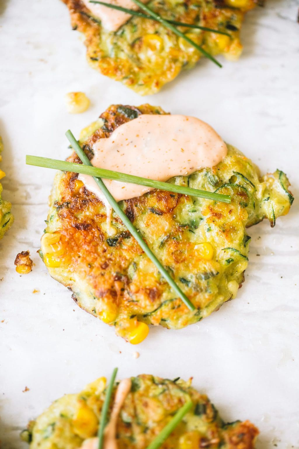 summer zucchini and corn fritters topped with creamy sauce and chives