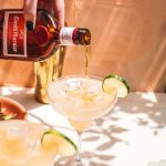 hand pouring grand marnier floater on top of cadillac margarita