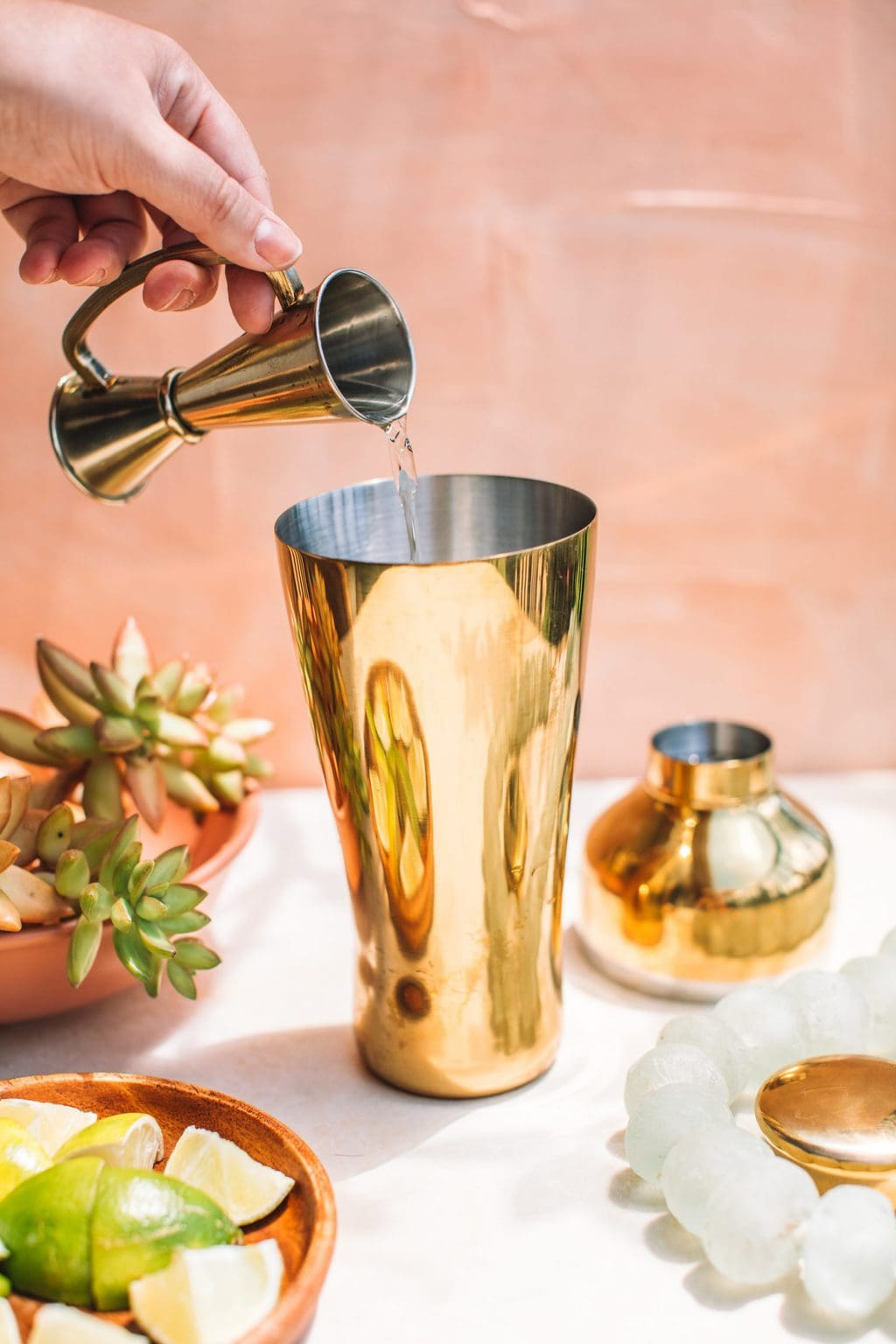hand pouring liquor into gold cocktail shaker from one ounce pourer