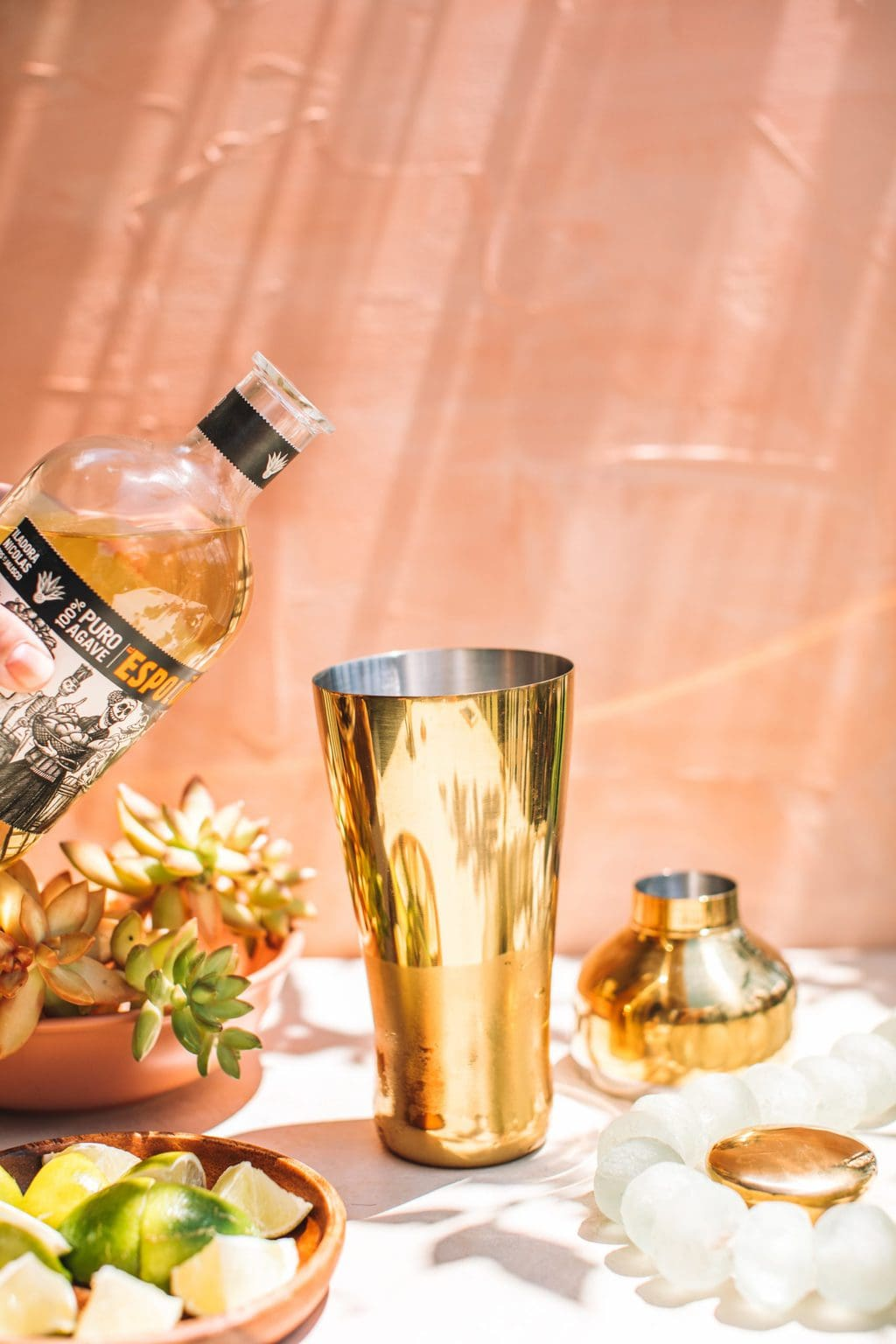 reposado tequila bottle hovering over gold cocktail shaker
