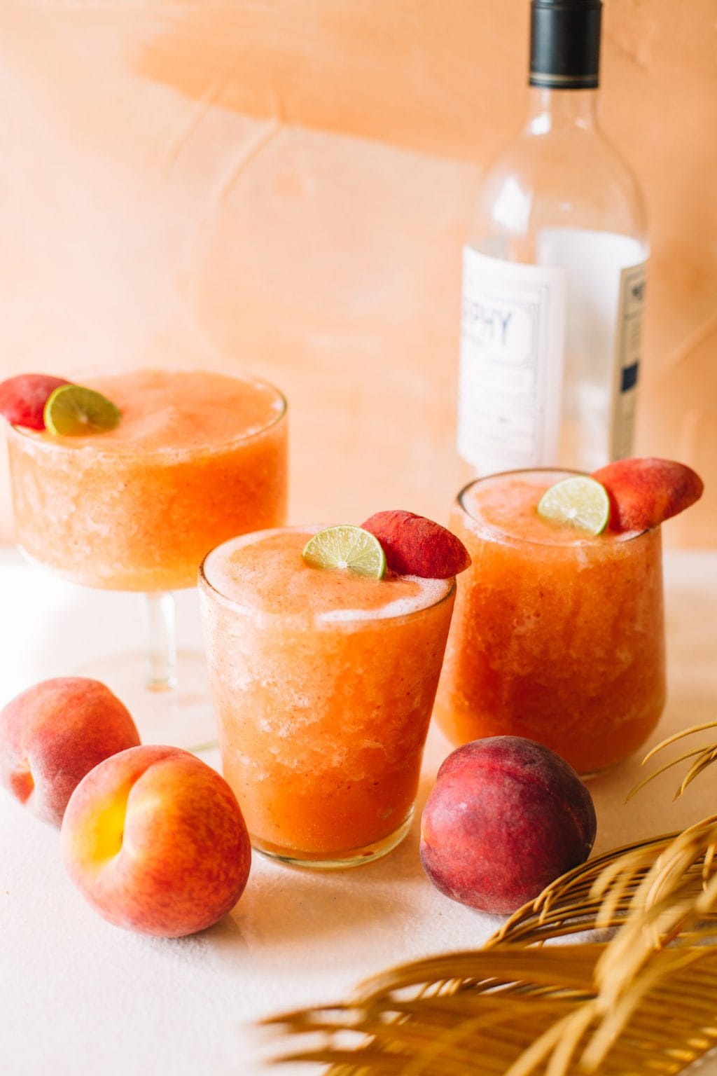 frozen peach strawberry white wine slushies in glasses with peach garnish