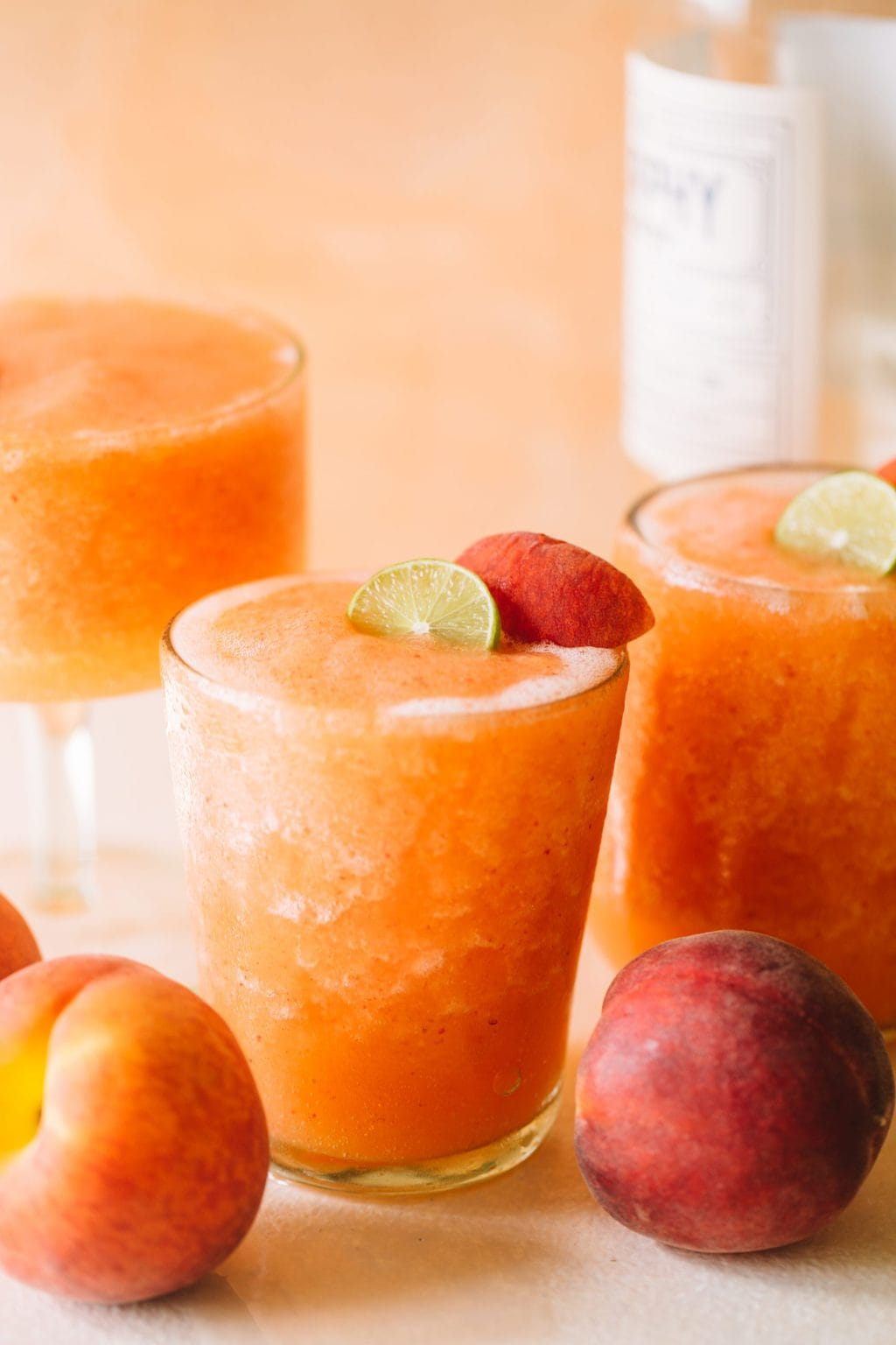 frozen peach white wine slushies in glasses with peach garnish