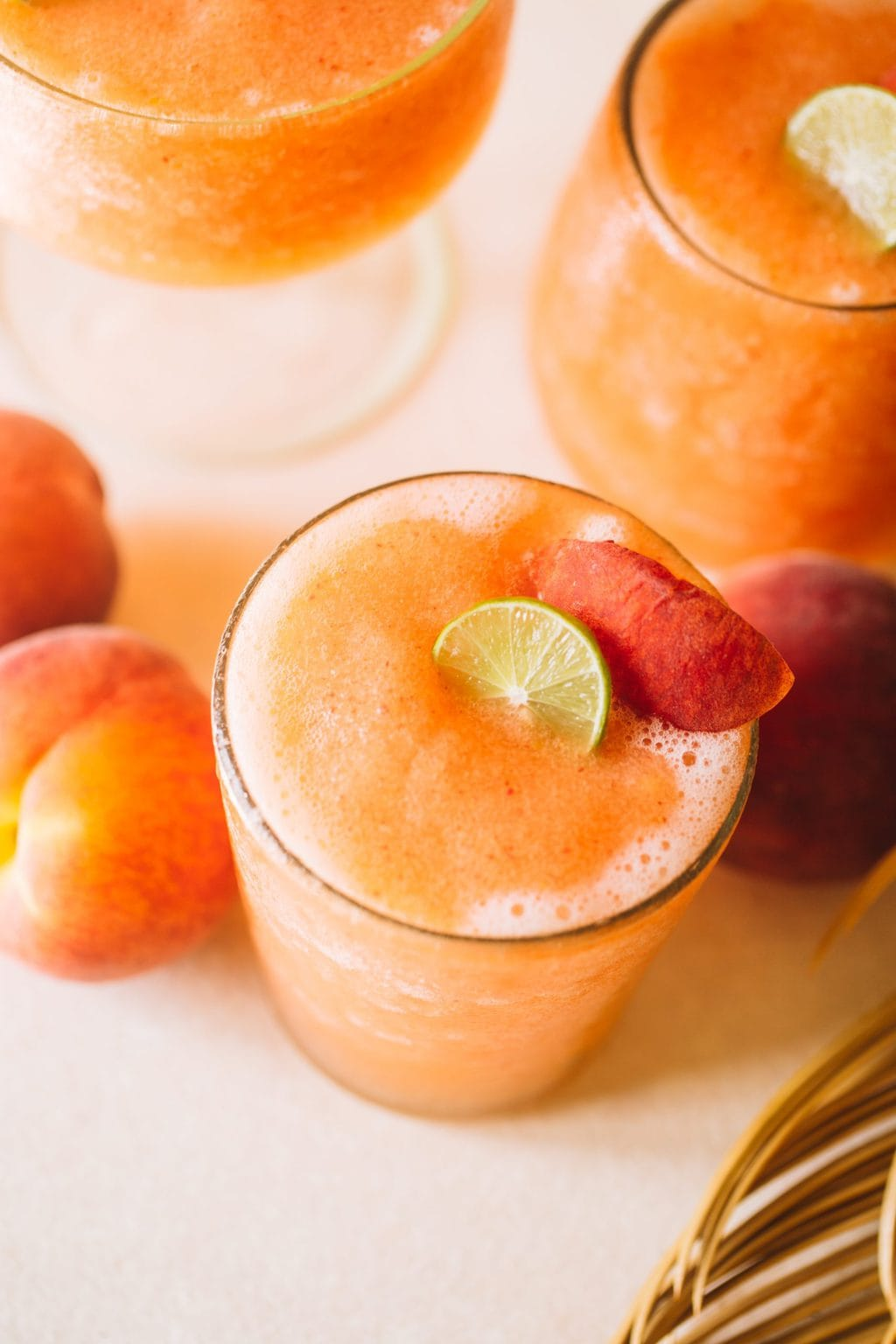 easy frozen peach cocktail recipe in glass with peach garnish