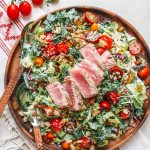 Kale Caesar Chopped Salad served on a wooden plate with a seared ahi tuna steak on top.