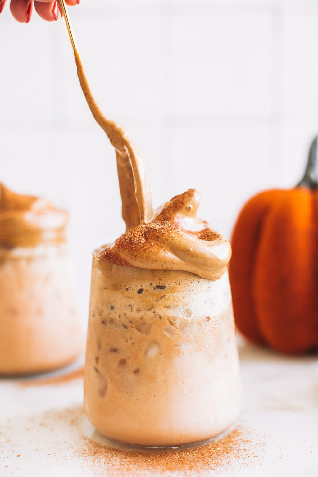 Glass filled with pumpkin milk topped with whipped coffee.