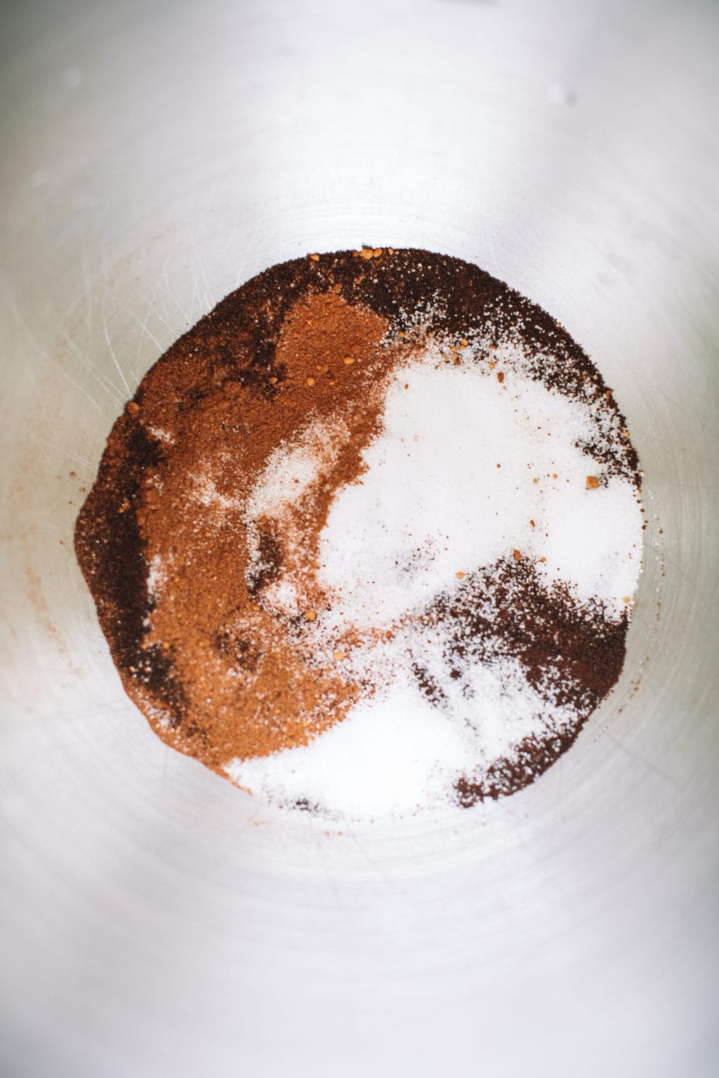 A mixing bowl filled with instant espresso, sugar, and pumpkin spice.