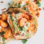 easy shrimp taco recipe with cilantro lime slaw in charred corn tortillas on white surface