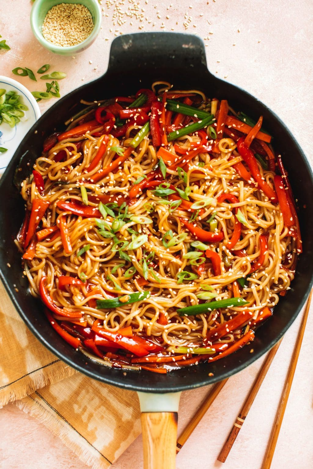 lo mein noodles and vegetables stir fried in cast iron pan with chopsticks