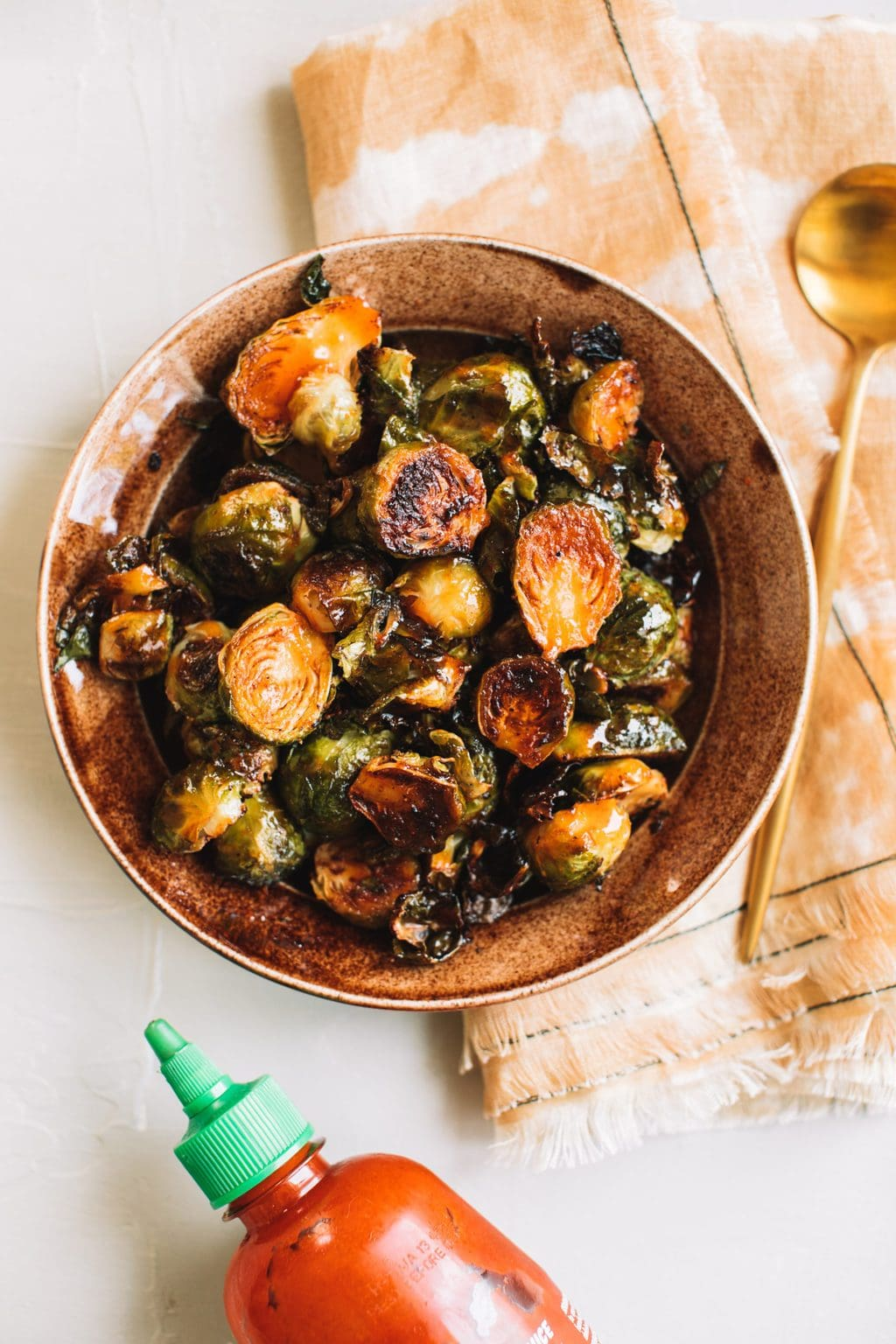 crisp honey sriracha brussels sprouts in brown bowl with gold spoon on the side