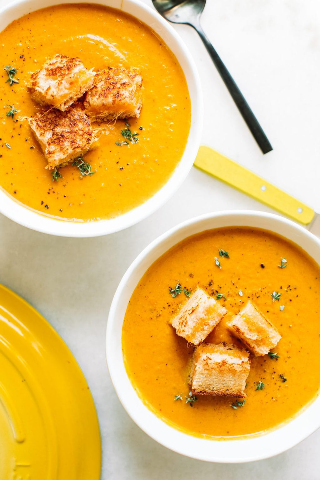 creamy pumpkin soup recipe in two white bowls with grilled cheese croutons