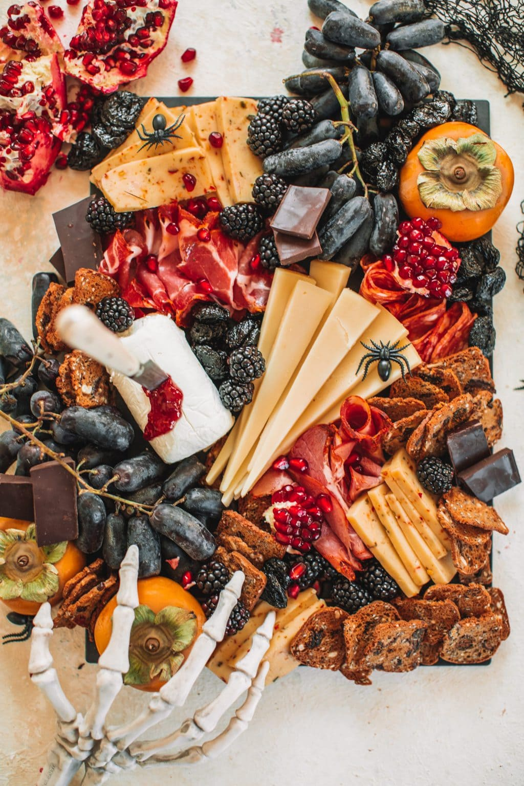 A spooky cheeseboard with cheeses, fruits, crackers and nuts.