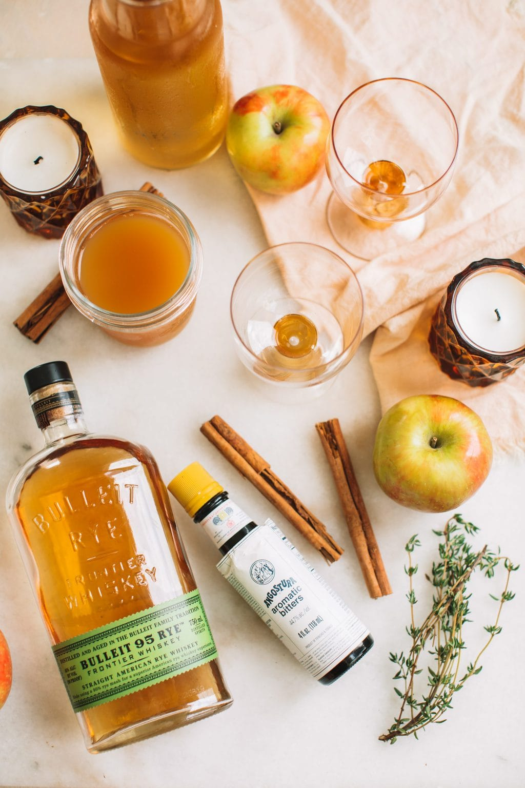 Two glass cubs, one glass mason jar, two candles, one apple, cinnamon sticks, a bottle of Bullet bourbon, and a bottle of apple cider
