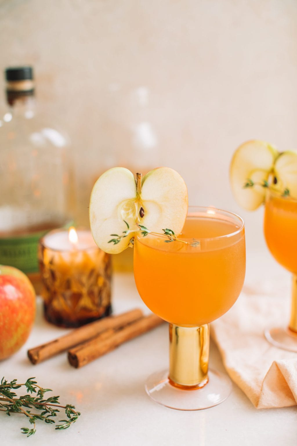 A glass cup with orange liquid and an apple slice garnish.