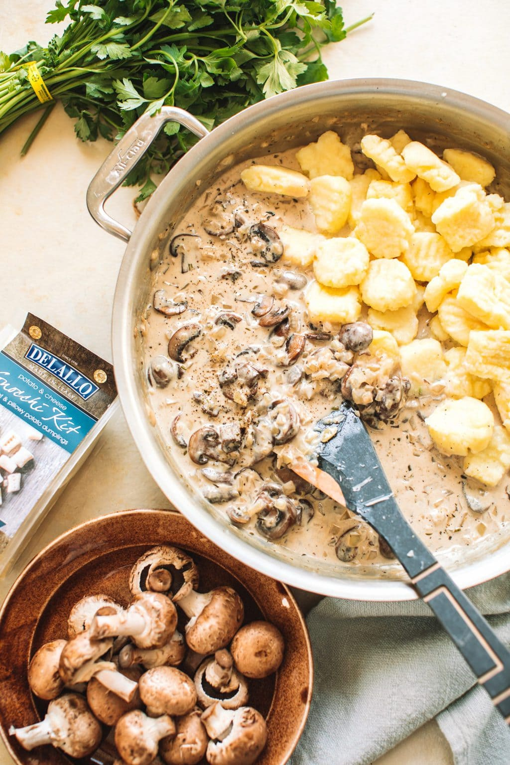 Mushrooms and gnocchi in a cream sauce garnished with parsley in a skillet.