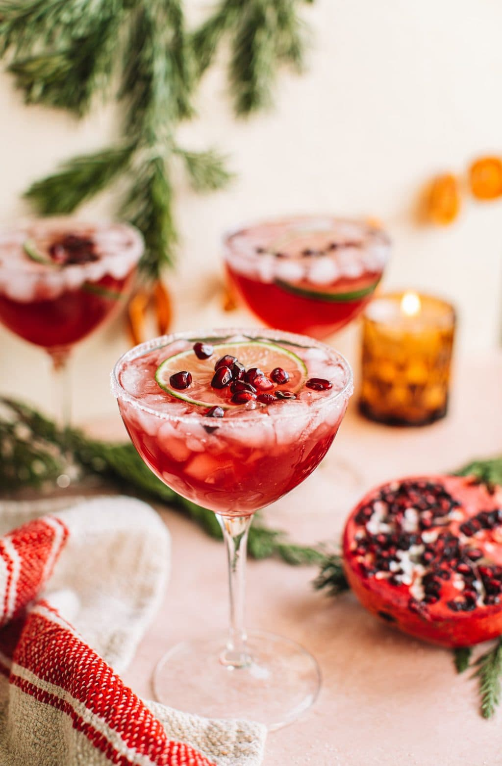 Cocktail glass filled with pomegranate christmas margarita on holiday tablescape