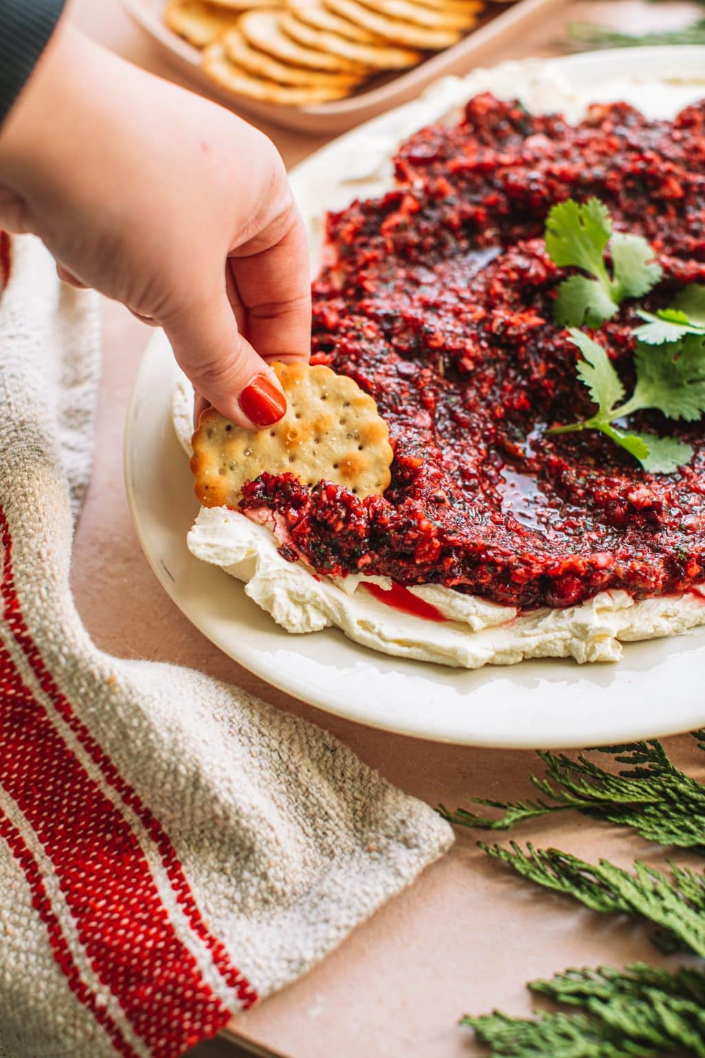 Hand dipping cracker in red jalapeno cranberry dip with cream cheese spread on white plate next to dish of crackers