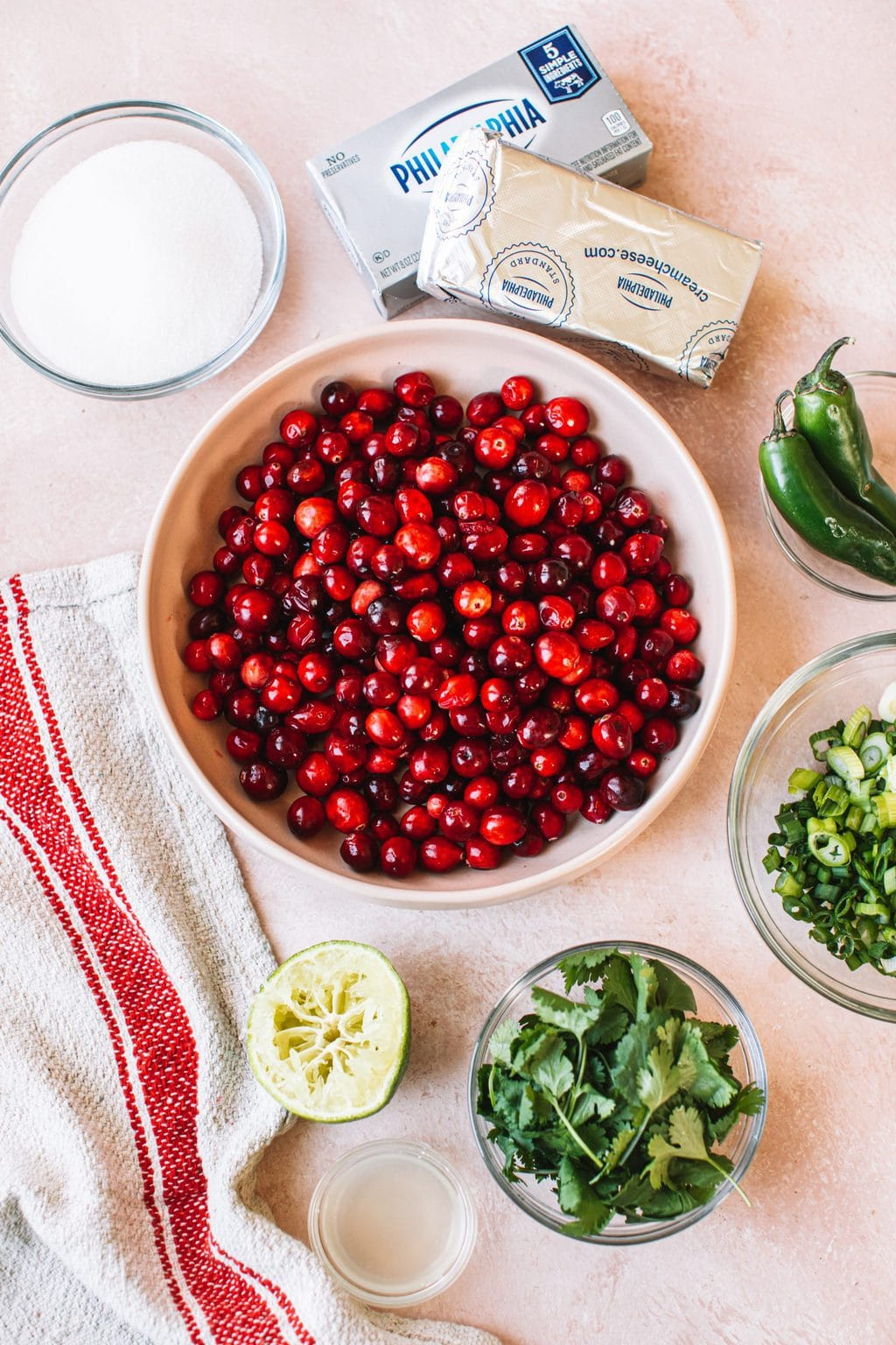Ingredients top shot, bowl of red cranberries, small bowls of cilantro, jalapeños, chopped onion, and sugar, and two blocks of Philadelphia cream cheese
