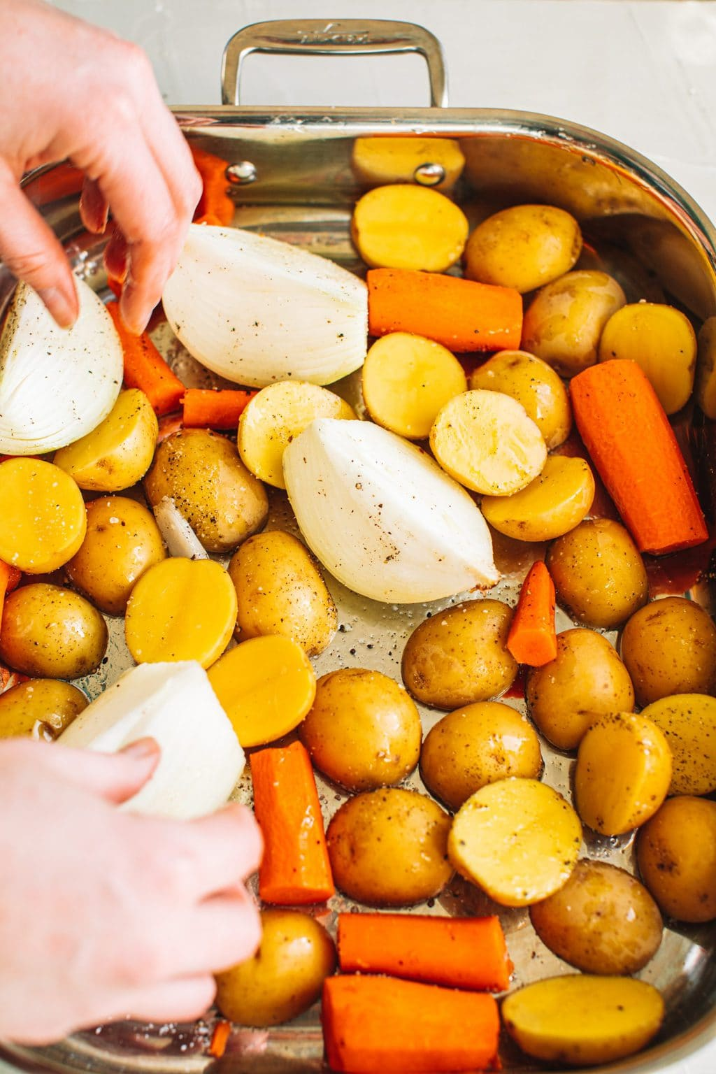 Small Yukon potatoes, chopped carrots, and quartered onions arranged in a roasting dish
