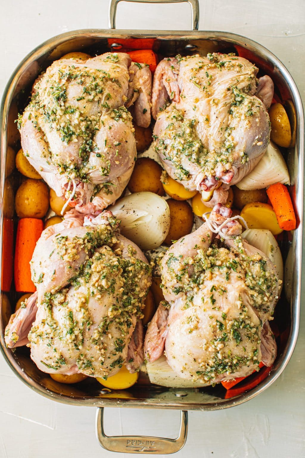 Four cornish hens set on top of carrots, onions and potatoes in a roasting dish before going into the oven