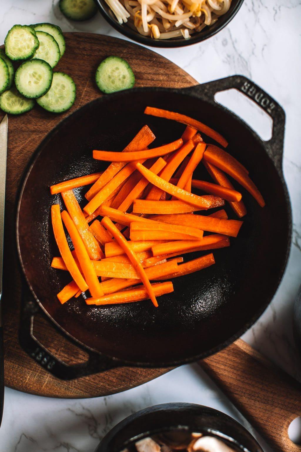 top shot of sliced carrots in black skillet
