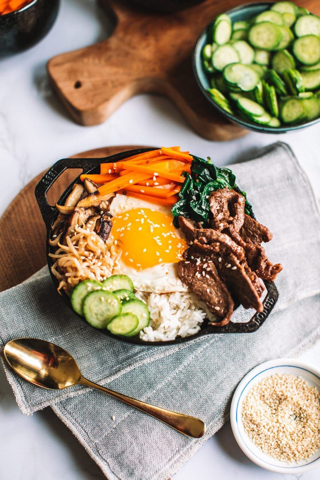 top shot of bibimbap bowl topped with sliced meat, egg, carrots, and other veggies
