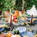 moroccan theme table scape with blue plates, yellow napkins, and a candle set outdoors on a wooden table
