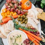 top shot of hummus and fruit platter on wooden table outdoors for moroccan night party