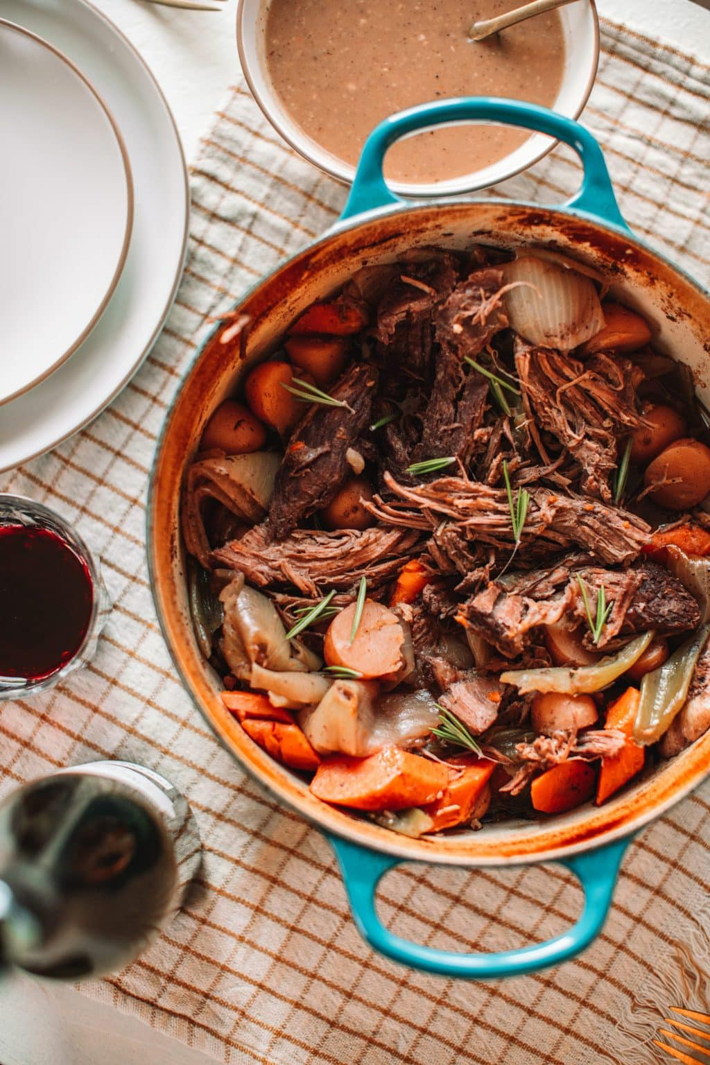 top shot of pot roast and vegetables in dutch oven pot with blue handles