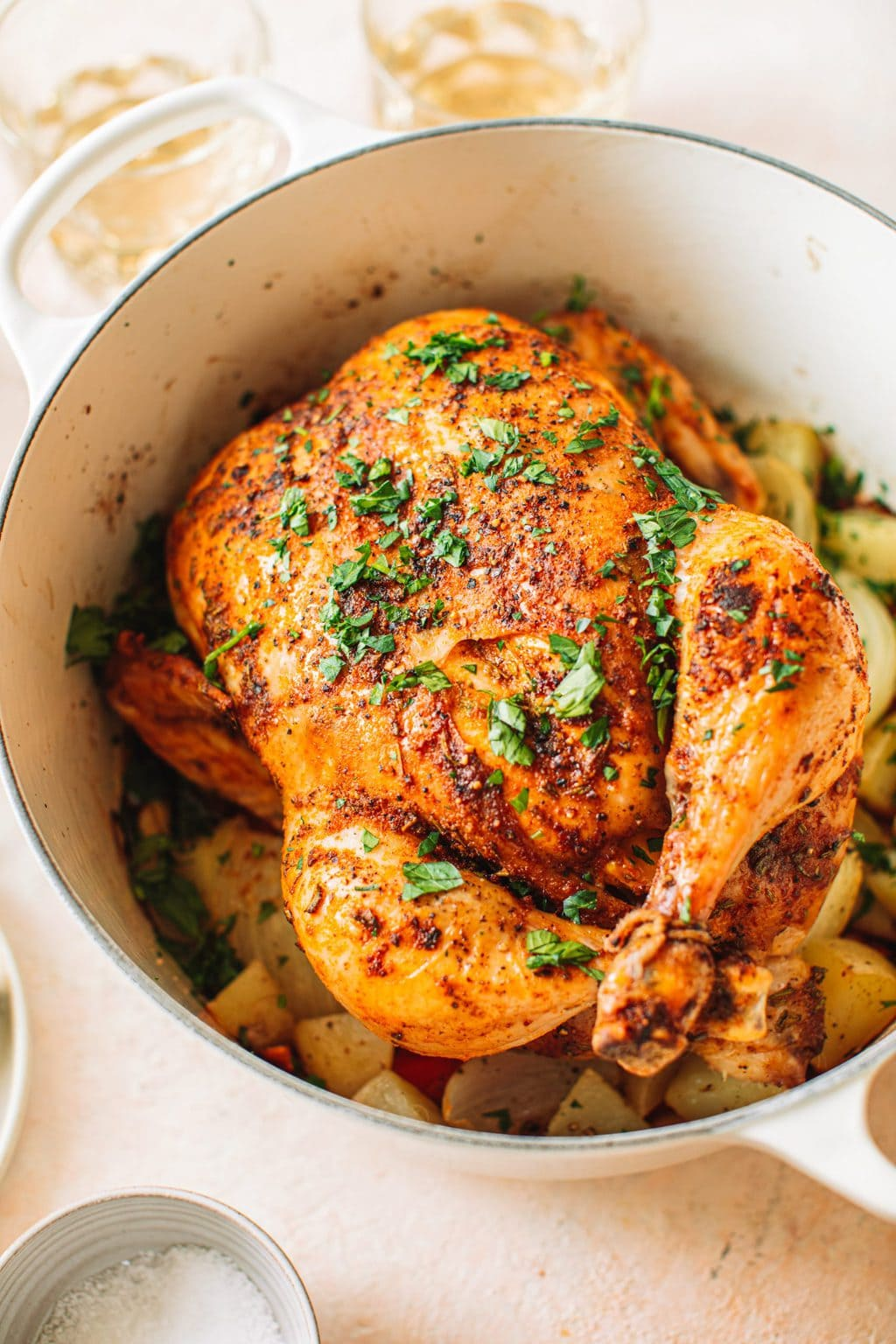 Top shot of roast chicken in dutch oven garnished with parsley in large pot.