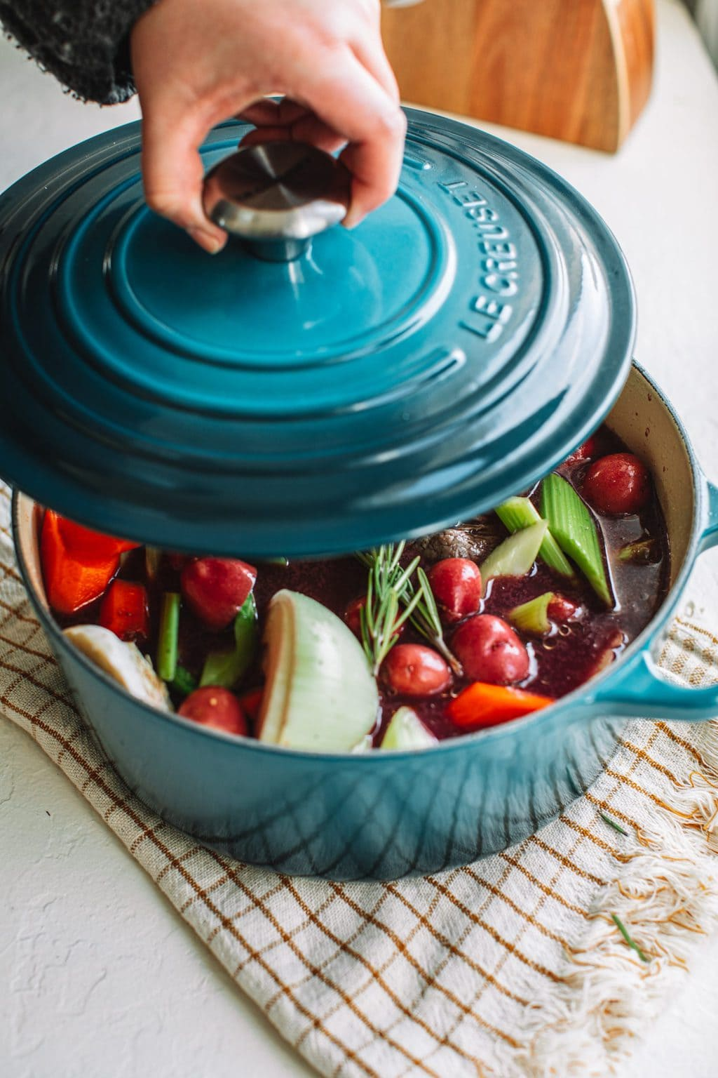 top shot of hand opening blue top to show pot roast and vegetables in light blue dutch oven