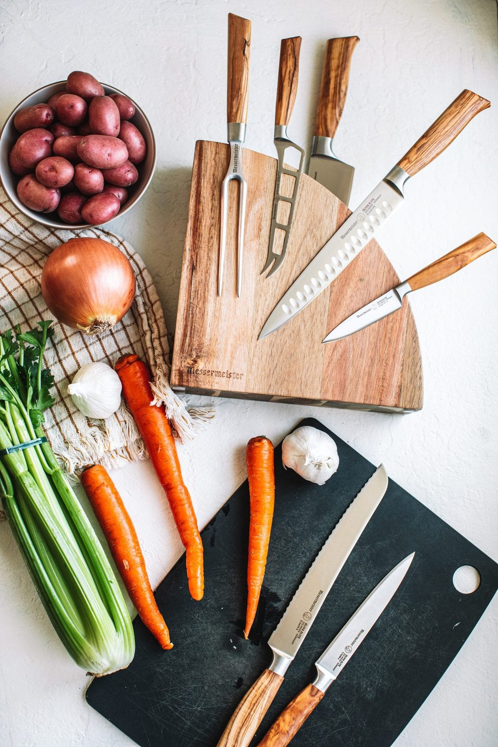 top shot of pot roast ingredients and cooking knives on white countertop