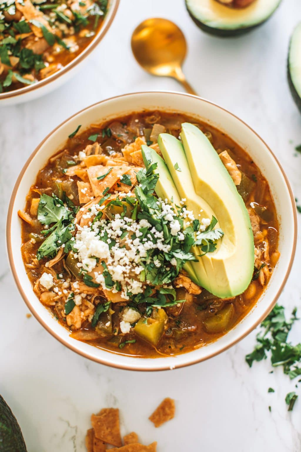 Chicken enchilada soup topped with tortilla chips, cotija cheese, cilantro and avocado slices.