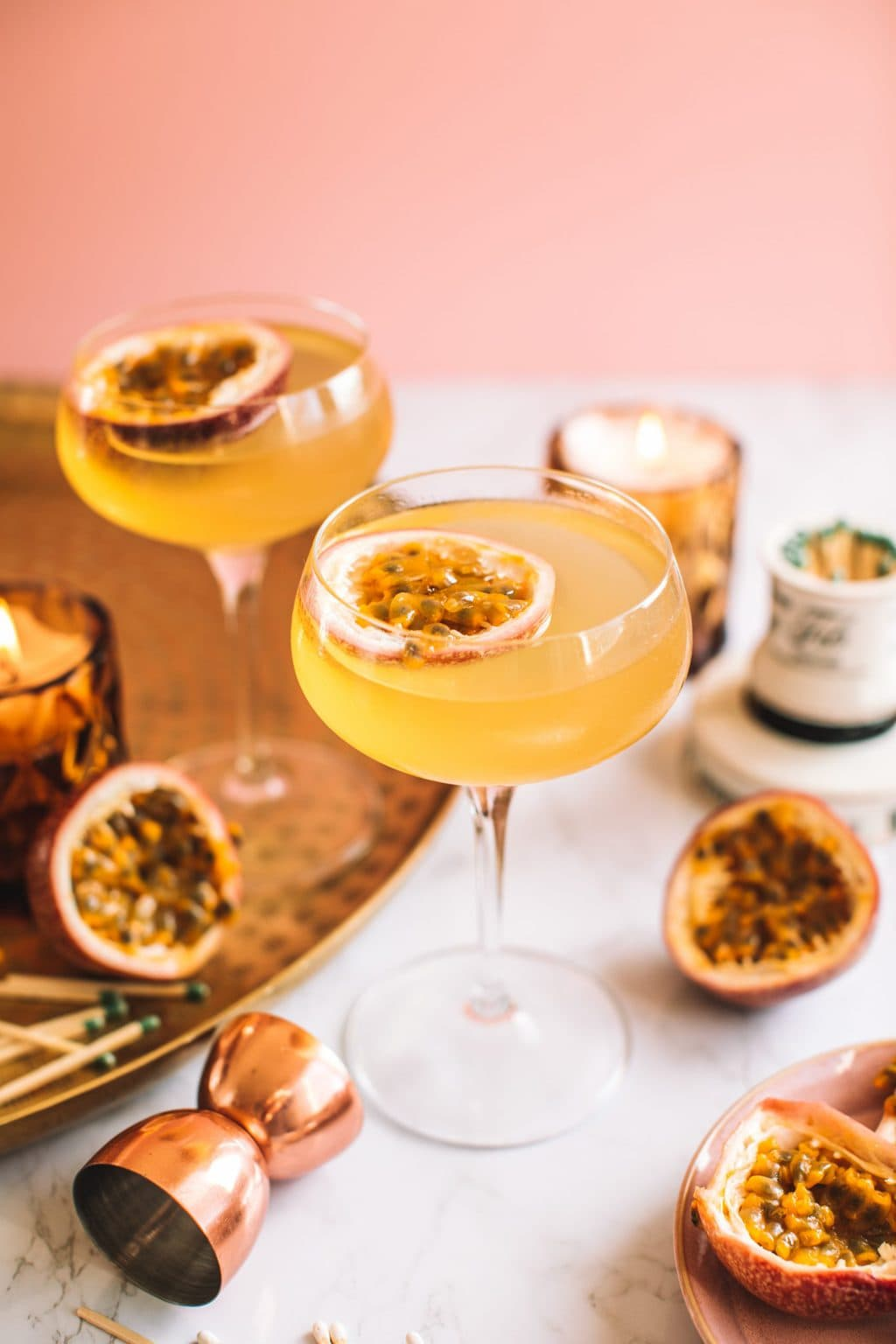 Passion fruit martini served in two glasses garnished with a passion fruit half.