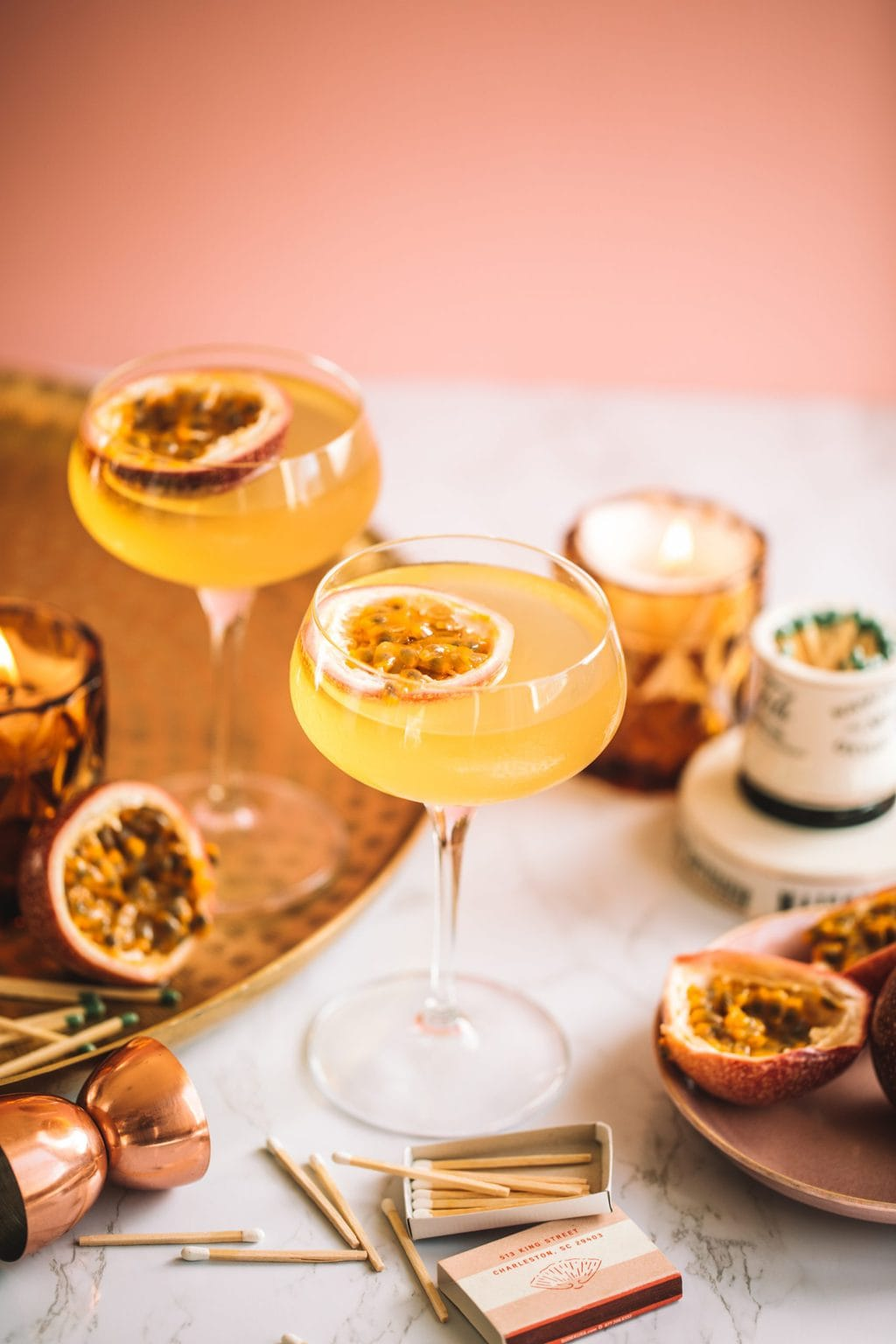 A passion fruit martini served in a coupe glass and a garnished with a passion fruit half.