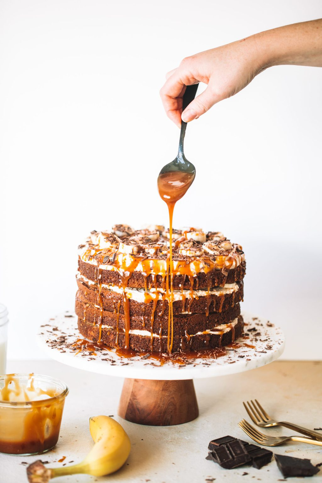 Woman holding spoon dripping caramel sauce onto banoffee cake.