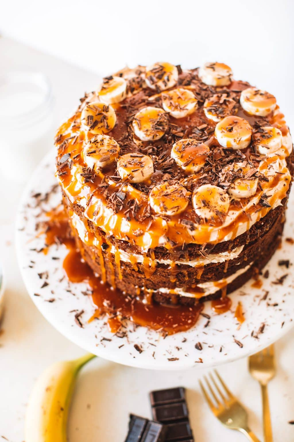Top shot of cake with caramel and bananas on top, sitting on cake stand.